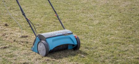 Gardener Operating Soil Aeration Machine on Grass Lawn. Foto de archivo