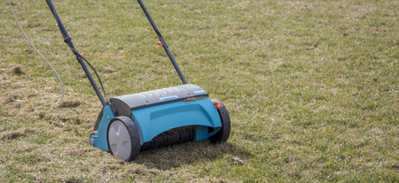Gardener Operating Soil Aeration Machine on Grass Lawn. Banque d'images