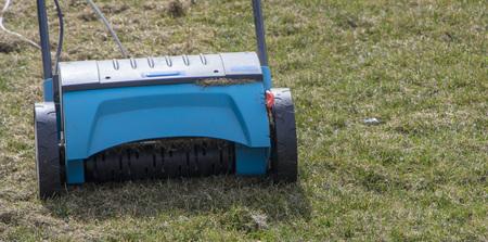 Gardener Operating Soil Aeration Machine on Grass Lawn. Archivio Fotografico