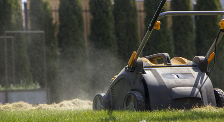 Gardener Operating Soil Aeration Machine on Grass Lawn Archivio Fotografico