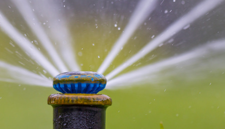 automatic sprinkler system watering the lawn on a background of green grass, close-up Stock fotó