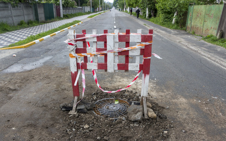 Repair of the road, Installed a protective color fence over the failed hatch. Stock Photo