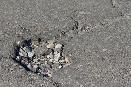 there are many potholes on the roadway close-up