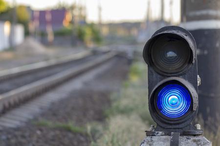 Traffic light on railway tracks. Blue light is on. Close up