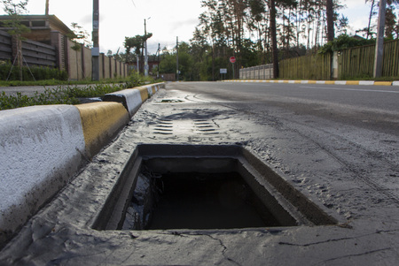 Pothole in asphalt near the sewer hatch, in the middle of the street. Stock Photo