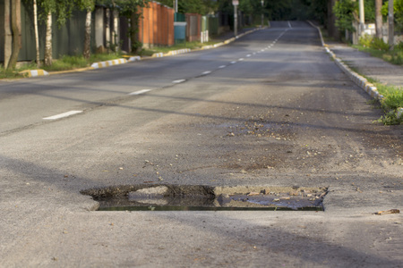 Pothole in asphalt near the sewer hatch, in the middle of the street. Stok Fotoğraf