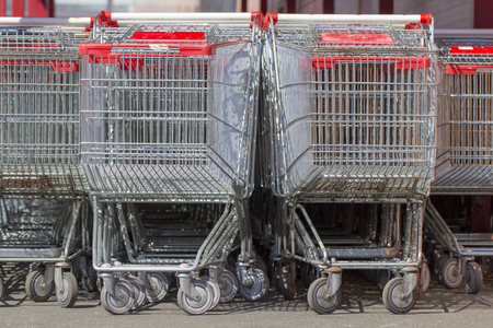 Supermarket shopping carts in a row in large supermarket store parking close up Banco de Imagens