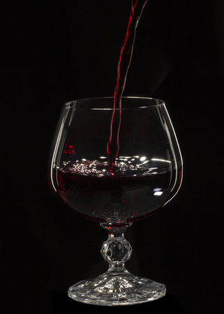 Glass still life image A glass of red wine in a glass on a black background close up