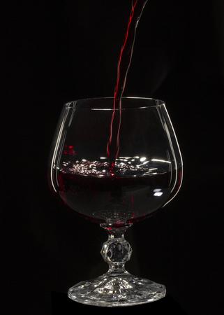 Glass still life immagine Un bicchiere di vino rosso in un bicchiere su sfondo nero da vicino Archivio Fotografico - 106797754