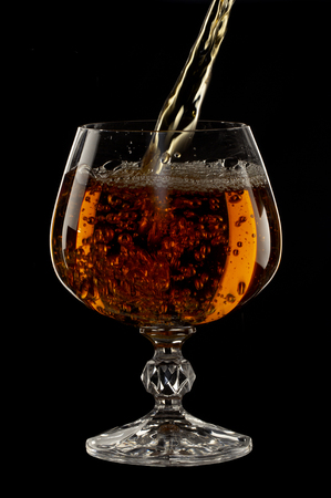 Cognac is poured into a glass, a spray of a drink, on a black background close up