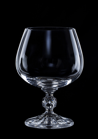 empty glass for cognac isolated over black background close up