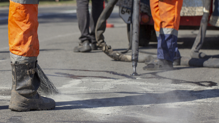 Workers repair the road, pour small cracks with bitumen to prevent further destruction of the road surface. Close up Stock fotó