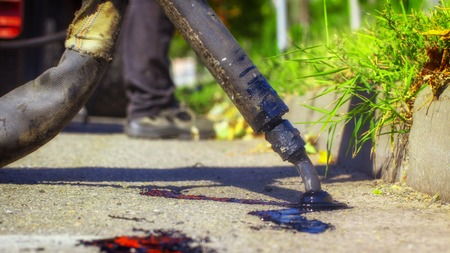 Workers repair the road, pour small cracks with bitumen to prevent further destruction of the road surface. Close up Stock Photo
