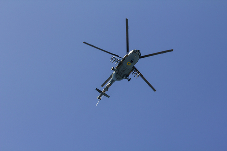 Military helicopter maneuvers in the blue sky. Stock Photo