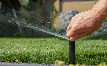 automatic sprinkler system watering the lawn on a background of green grass, close-up 写真素材