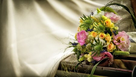 Wedding bouquet with roses on a wooden bench close up