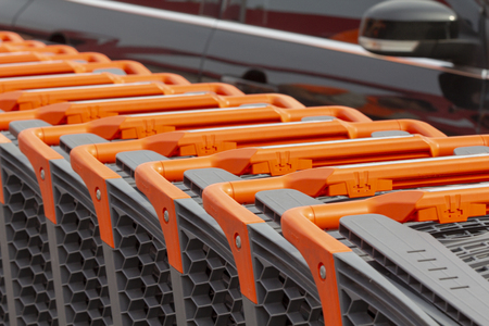 Supermarket shopping carts in a row in large supermarket store parking close up Stock Photo