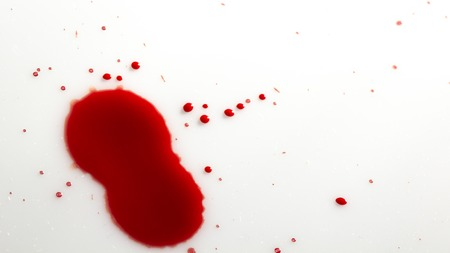 drops of red blood on white paper close up