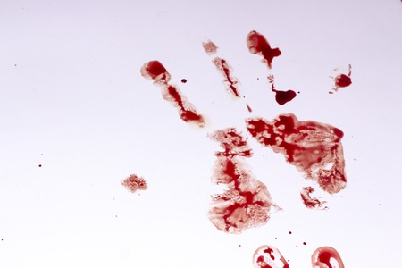 Red imprint of the bloody palm on a white background close up