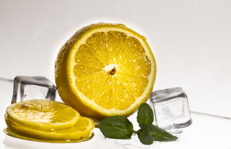 Fresh sliced lemon with glass and ice cubes. Close-up.