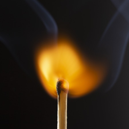 Burning wooden match with a red match head on a black background. Close up 写真素材