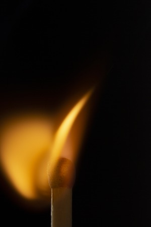 Burning wooden match with a red match head on a black background. Close up 免版税图像