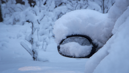 Snow-covered round mirror of a car standing early in the morning in the parking lot cloe up