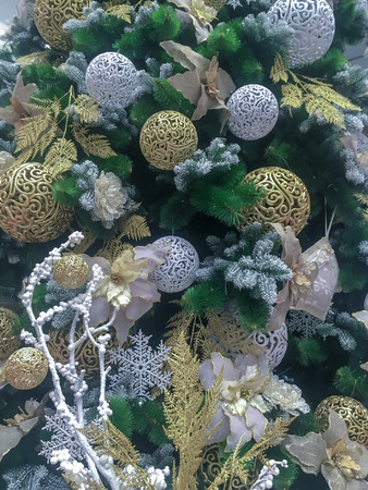Texture of plastic branches of the Christmas tree and decorations in silver tones Background