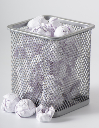 A trashcan full of crumpled paper on white background