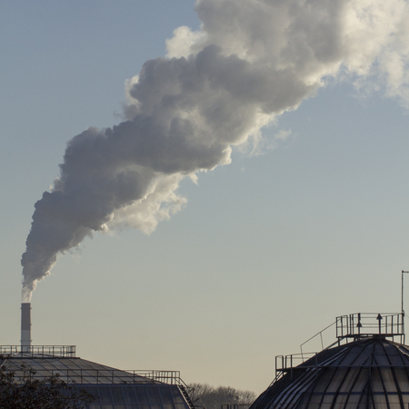 Pollution. Smoke from industrial chimneys against the blue sky Standard-Bild - 114048938