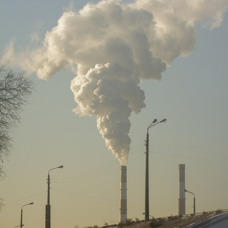 Pollution. Smoke from industrial chimneys against the blue sky Standard-Bild - 114048954