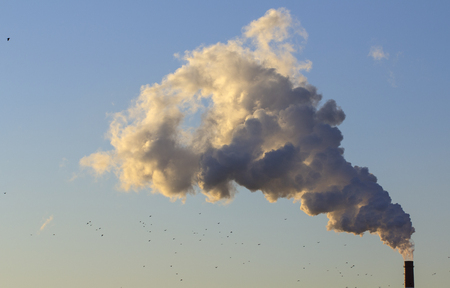 Pollution. Smoke from industrial chimneys against the blue sky Standard-Bild - 114048968