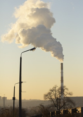 Pollution. Smoke from industrial chimneys against the blue sky Standard-Bild - 114048995