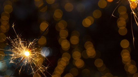 burning sparkler on bokeh background from lights of garland close up