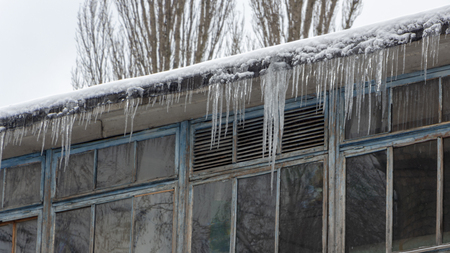 Icicles on the drainpipe and ditch. Incorrect installation of the drainage system, on which large icicles appear that pose a threat to the health and lives of people