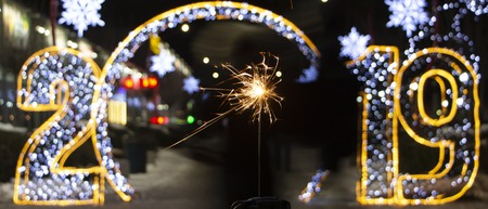 The inscription 2019 in Rasfokus, sparkler in the foreground, the concept of the new year background Stock Photo
