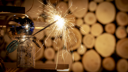 Rustic wooden wall with a sparkler and golden bokeh Christmas concept close up