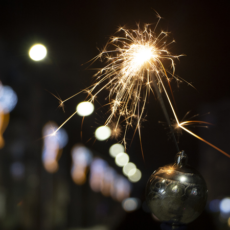 burning sparkler on bokeh background from lights of garland close up 版權商用圖片 - 114919544