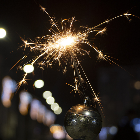 burning sparkler on bokeh background from lights of garland close up 版權商用圖片 - 114919545