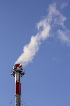 Pollution. Smoke from industrial chimneys against the blue sky Standard-Bild - 115722787