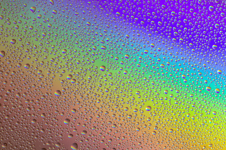 Drops of water on the glass, with the reflection of the rainbow. Background 스톡 콘텐츠