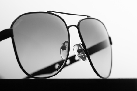 Black polarizing sunglasses in a metal frame on a black fabric background close up