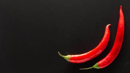 Red hot chili peppers on a black slate background texture close-up