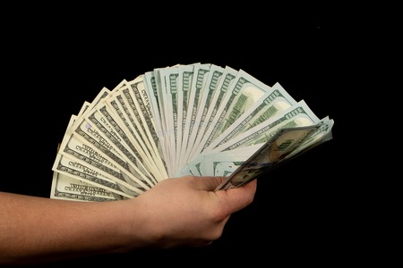 Fan of dollars in a male's hand on a black background, close up