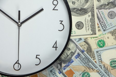 One hundred dollar bills and a white big clock, concept, time is money background close up