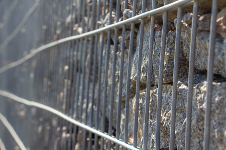 Gabion, a stone wall with a metal grid of gray granite texture background Banque d'images - 122337998