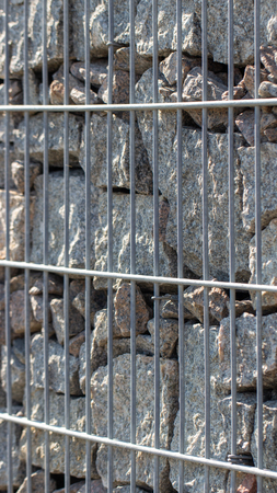 Gabion, a stone wall with a metal grid of gray granite texture background