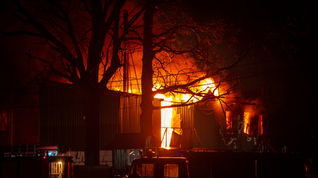 Fire in factory building at night. Burned by fire industrial warehouse.