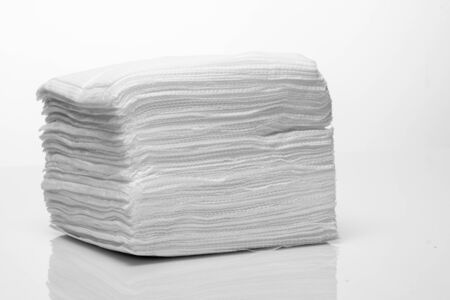 A stack of new white paper napkins on a white background close up