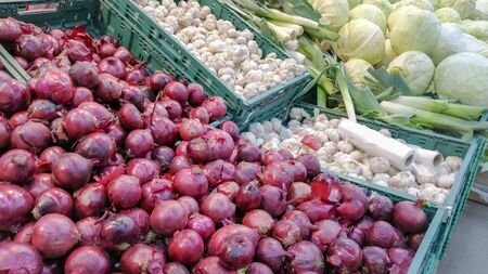 Red onions on the shop window among other vegetables background